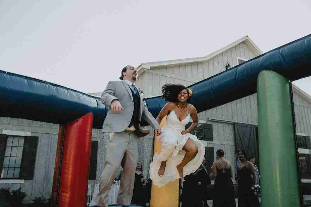 Bride and Groom Jumping in Bouncy House at Sweet Magnolia Estate NC Wedding