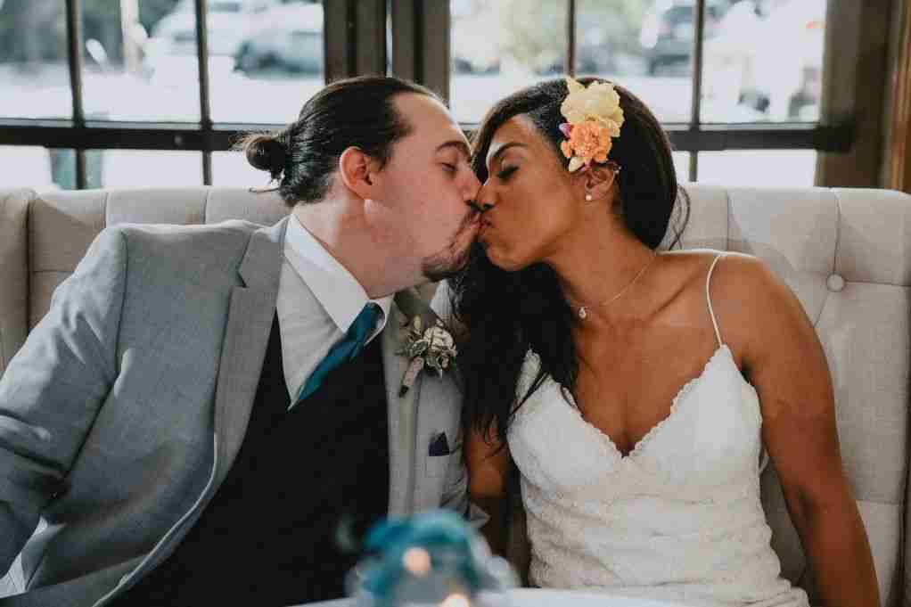 Newlyweds, Daniel and Kayla kiss during her wedding reception at Sweet Magnolia Estate