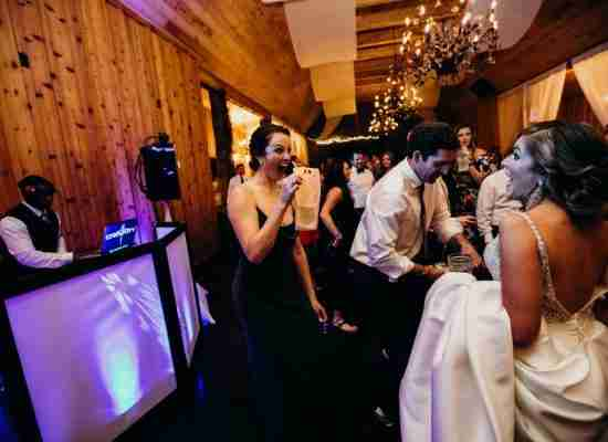 Bride laughing with guest holding a flask at her Wedding Reception with DJ Creativity